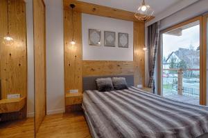 A bed or beds in a room at Apartament Góralska Nuta jacuzzi Centrum