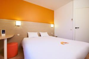 A bed or beds in a room at Premiere Classe Bordeaux Nord - Lac