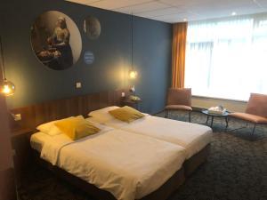 A bed or beds in a room at Hotel de Koophandel