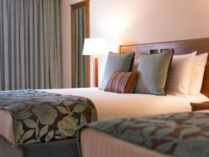 A bed or beds in a room at Garryvoe Hotel