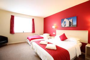 A bed or beds in a room at Wookey Hole Hotel