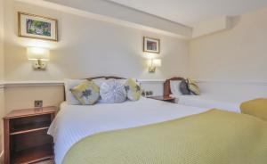 A bed or beds in a room at Bushtown Hotel & Spa