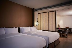A bed or beds in a room at Silks Place Tainan