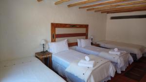 Una cama o camas en una habitación de Del Amauta Hosteria