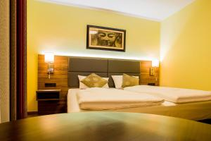 A bed or beds in a room at Naam Hotel & Apartment Frankfurt City-Messe Airport