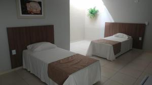 A bed or beds in a room at Pousada Recanto de Fátima
