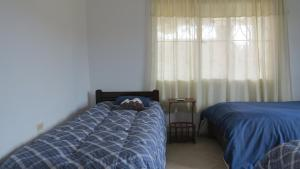 A bed or beds in a room at Hostal Casa Lantana