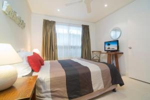 A bed or beds in a room at Plantation 2 - Absolute Beachfront