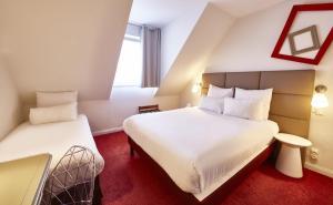 Ein Bett oder Betten in einem Zimmer der Unterkunft Best Western Plus Au cheval Blanc à Mulhouse