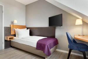 A bed or beds in a room at Ramada by Wyndham München Airport