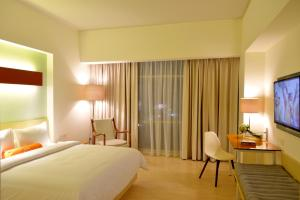 A bed or beds in a room at HARRIS Hotel & Conventions Bekasi