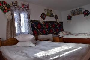 A bed or beds in a room at Pensiunea Maramu