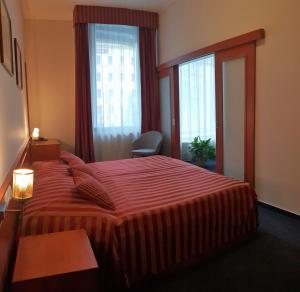 A bed or beds in a room at Hotel Beránek