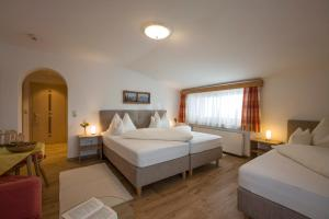A bed or beds in a room at Hotel Theresia Garni