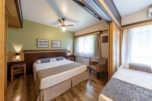 A bed or beds in a room at Toscana Gramado Flat