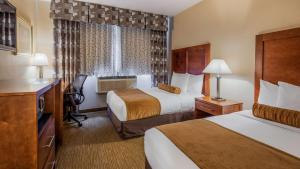 A bed or beds in a room at Best Western PLUS Arena Hotel