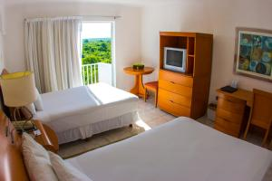 A bed or beds in a room at Coral Princess Hotel & Dive Resort