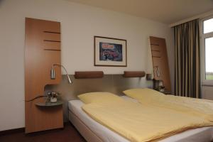 A bed or beds in a room at Hotel Motorsport Arena