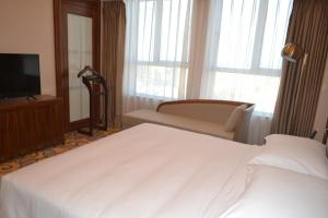 A bed or beds in a room at Primus Hotel Kaloum
