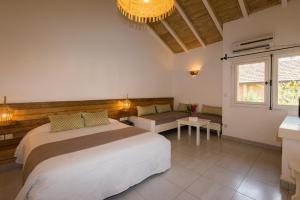 Een bed of bedden in een kamer bij Le Saly Hotel & Hotel Club Filaos