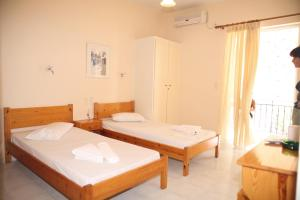 A bed or beds in a room at Polyxenis Rooms