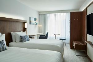 A bed or beds in a room at Courtyard by Marriott Luton Airport