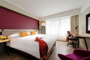 A bed or beds in a room at Mercure Ariosto Lima