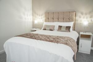 A bed or beds in a room at TLK Apartments and Hotel - Orpington