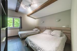 A bed or beds in a room at Hôtel du Rocher