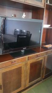 Uma TV ou centro de entretenimento em Apartamento Peruíbe