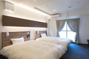 Tempat tidur dalam kamar di HOTEL CITY INN WAKAYAMA Wakayama-Ekimae