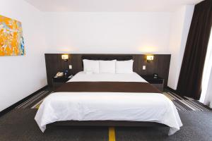 A bed or beds in a room at Costa del Sol Wyndham Lima Airport