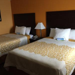 A bed or beds in a room at Days Inn by Wyndham Queensbury/Lake George