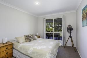 A bed or beds in a room at 14 Zircon Street - Centrally located family home with covered deck, close to patrolled beach & shops