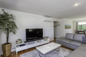A seating area at 14 Zircon Street - Centrally located family home with covered deck, close to patrolled beach & shops