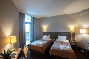 Кровать или кровати в номере Бизнес-отель Золотой Затон