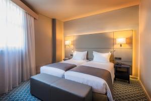 Ein Bett oder Betten in einem Zimmer der Unterkunft Hotel Dom Henrique - Downtown