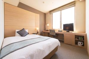 A bed or beds in a room at K's Street Hotel Miyazaki