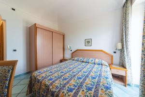 A bed or beds in a room at La Capannina - Hotel & Apartments