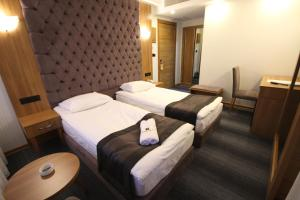 A bed or beds in a room at Grand Silay Hotel