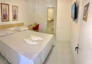 A bed or beds in a room at Pousada Mel