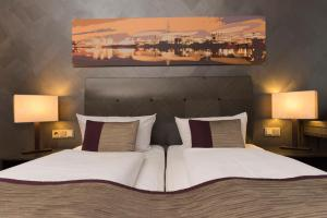 A bed or beds in a room at Wyndham Duisburger Hof