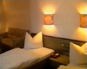 A bed or beds in a room at Hotel Merkur Garni