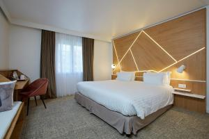 A bed or beds in a room at Best Western Plus Paris Meudon Ermitage