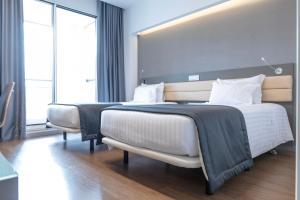En eller flere senge i et værelse på Hotel Alif Campo Pequeno