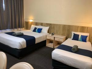 A bed or beds in a room at Wattle Tree Motel