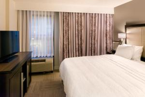 A bed or beds in a room at Hampton Inn & Suites Orlando-East UCF