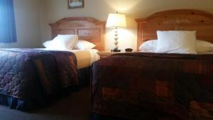 A bed or beds in a room at Lakeshore Inn & Suites