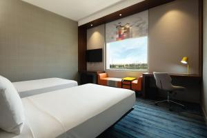 A bed or beds in a room at Aloft Dubai South