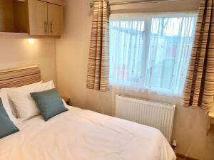 A bed or beds in a room at Heacham Gold Caravan